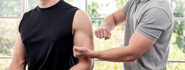 Terapeuta daje masażowi atleta męski pacjent dla sport fizycznej terapii pojęcia