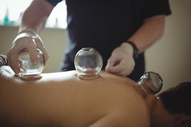 Terapeuta daje terapię bańką dla człowieka