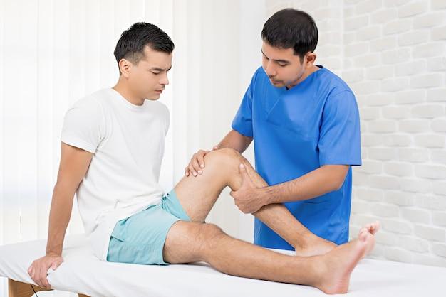 Terapeuta lecząc rannych kolana męskiego pacjenta w szpitalu