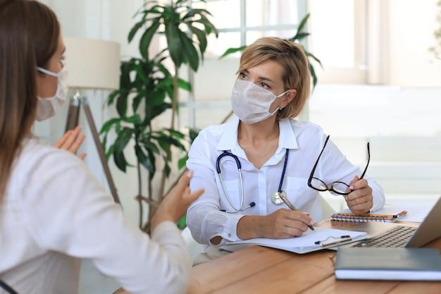 Terapeuta lekarz kobiet w średnim wieku w masce medycznej na konsultacji z pacjentem w biurze.