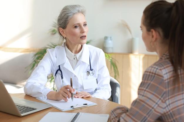 Terapeuta lekarz kobiet w średnim wieku w porozumieniu z pacjentem w gabinecie.