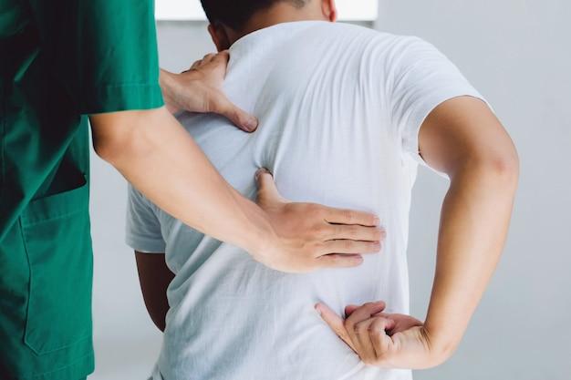 Terapeuta-lekarz robi leczenie na plecach mężczyzny. pacjent z bólem pleców, leczenie, lekarz, masaż na zespół biura łagodzącego ból pleców