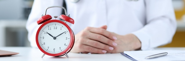 Terapeuta lekarz siedzi w biurze przed czerwonym budzikiem zbliżenie lekarze koncepcja harmonogramu