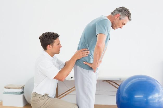 Terapeuta masuje mans dolnej powrót w szpitalu siłowni