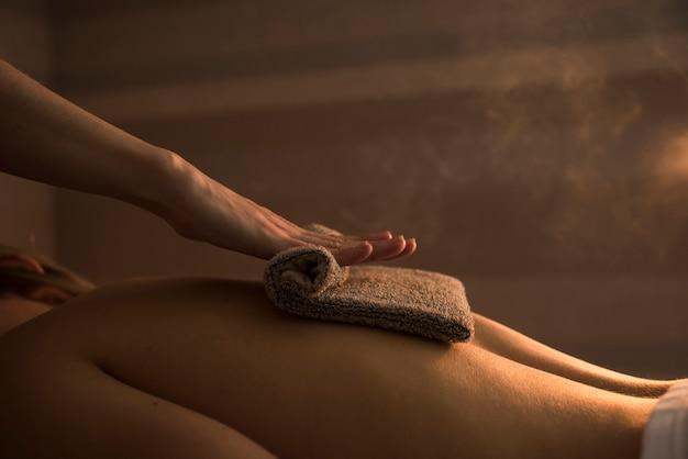 Terapeuta masuje plecy kobiety z gorącym ręcznikiem w spa