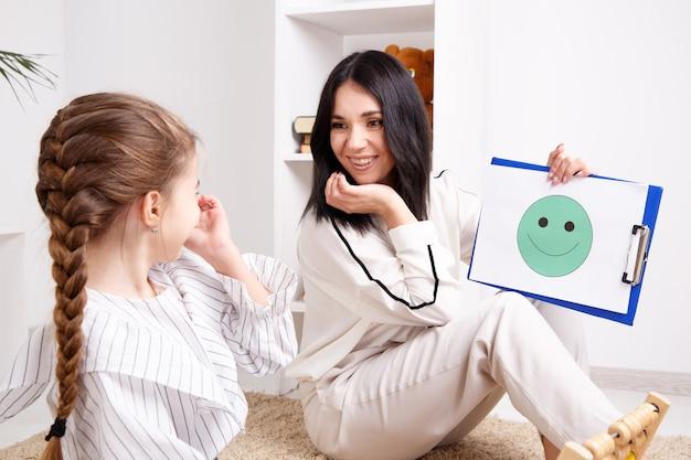 Terapeuta pokazujący małemu pacjentowi uśmiechniętą twarz na papierze. koncepcja psychologa.