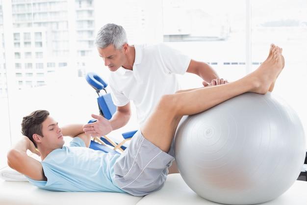 Terapeuta pomaga jego pacjentowi z ćwiczenie piłką w medycznym biurze