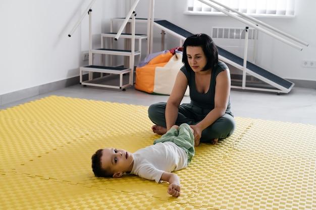 Terapeuta prowadzący rehabilitację dzieci z mózgowym porażeniem dziecięcym