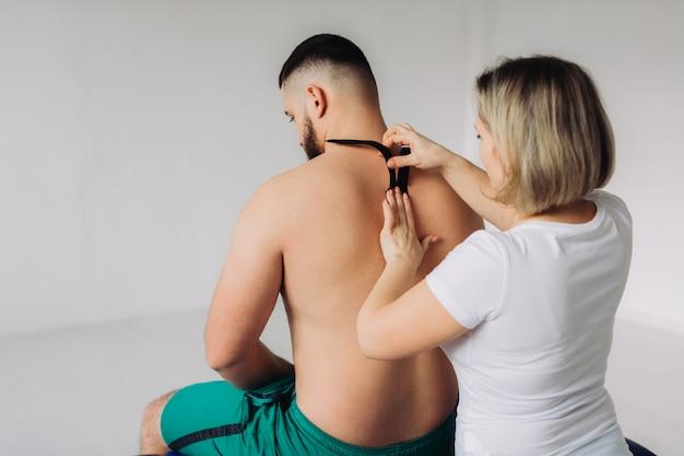 Terapeuta przykleja taśmę kinezjologiczną do szyi pacjenta.