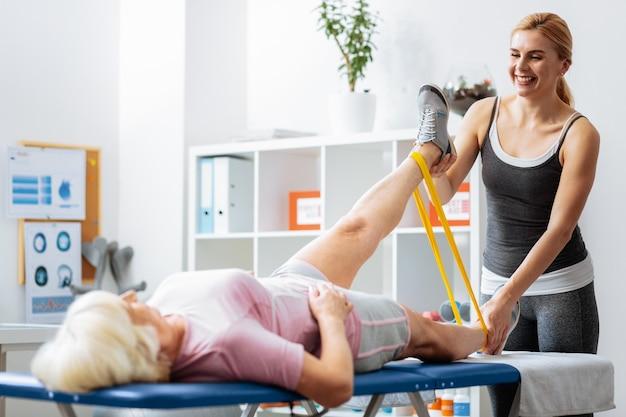 Terapeuta rehabilitacji. radosna, szczęśliwa kobieta będąca w świetnym nastroju podczas pracy jako terapeutka rehabilitacyjna