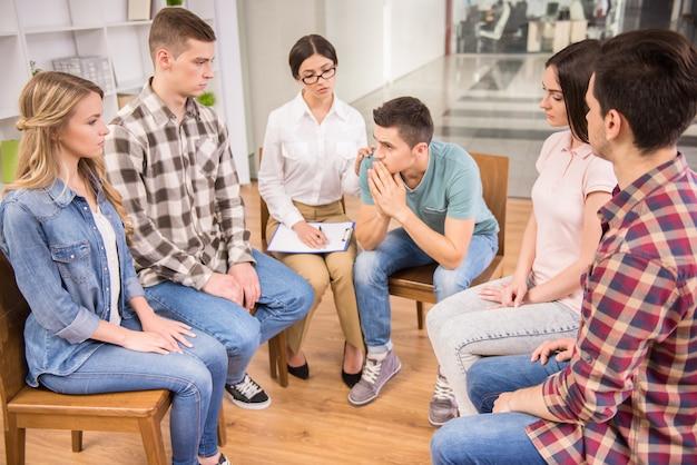 Terapeuta rozmawia z grupą rehabilitacyjną podczas sesji terapeutycznej.