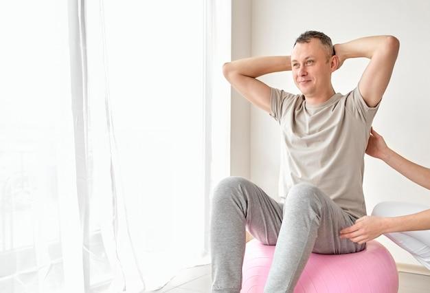 Terapeuta w trakcie fizjoterapii z pacjentem płci męskiej
