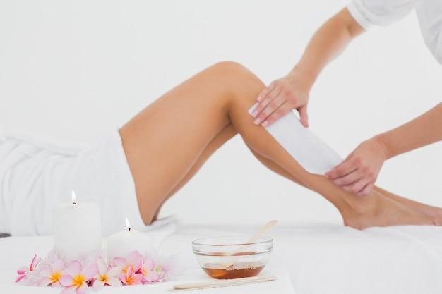 Terapeuta woskowanie nogi kobiety w centrum spa
