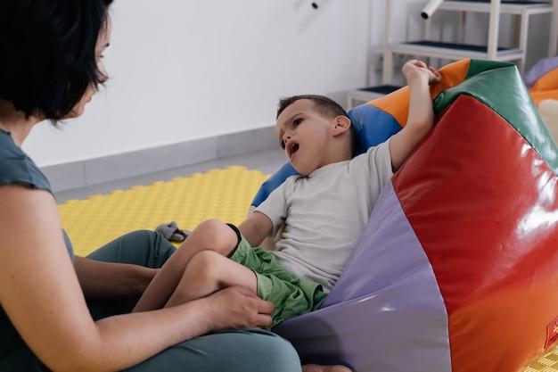 Terapeuta wykonujący ćwiczenia na macie z dzieckiem niepełnosprawnym