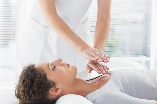 Terapeuta wykonujący reiki nad kobietą