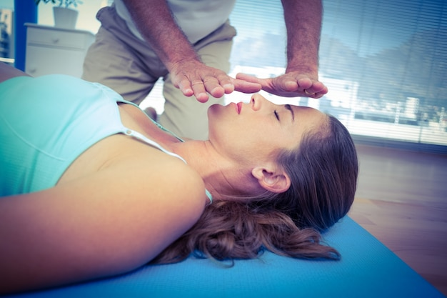 Terapeuta wykonuje reiki na młodej kobiecie