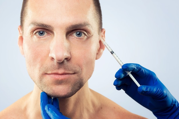 Terapia botulinowa. zbliżenie dłoni osoby wstrzykiwanie strzykawki z botoksem do leczenia twarzy. estetoks