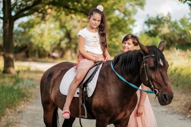 Terapia dziecięca na spacer z koniem. emocjonalny kontakt z koniem. spacer z matką i córką w lecie w parku z koniem.