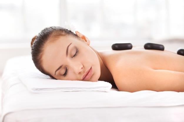 Terapia gorącymi kamieniami. widok z boku atrakcyjnej młodej kobiety leżącej z przodu i trzymającej oczy zamknięte z kamieniami spa na plecach