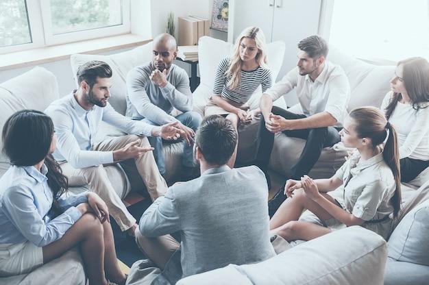 Terapia grupowa. grupa młodych ludzi siedzących w kręgu, podczas gdy jeden mężczyzna mówi coś i gestykuluje