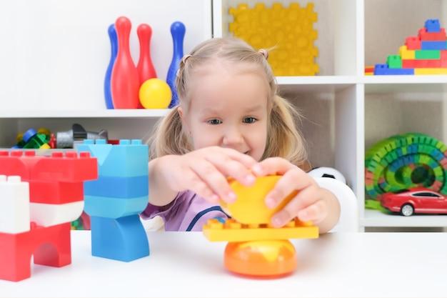 Terapia logopedyczna, rozwój umiejętności motorycznych. dziewczyna grająca w konstruktora, szczęśliwe dziecko