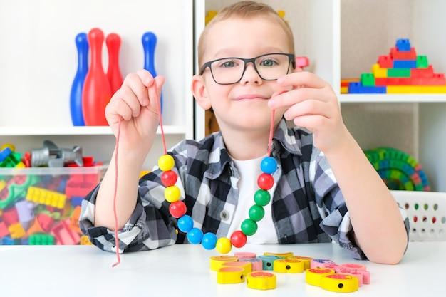 Terapia logopedyczna, rozwój umiejętności motorycznych. maluch chłopiec nawleka koraliki na sznurek. wesołe dziecko