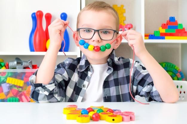 Terapia logopedyczna, rozwój umiejętności motorycznych. maluch chłopiec nawleka koraliki na sznurku. wesołe dziecko