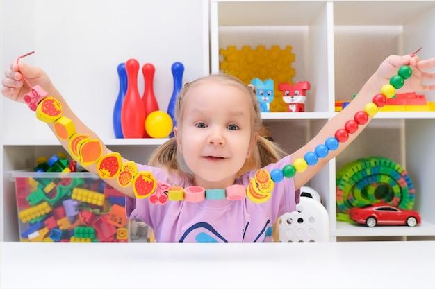 Terapia logopedyczna, rozwój umiejętności motorycznych. maluch dziewczyna nawleka koraliki na sznurku.
