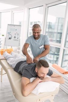 Terapia masażem. przyjemny, wesoły mężczyzna podczas masażu podczas wizyty w centrum rehabilitacji