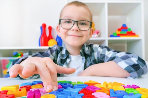 Terapia mowy. maluch chłopiec z literami. zajęcia z logopedą.