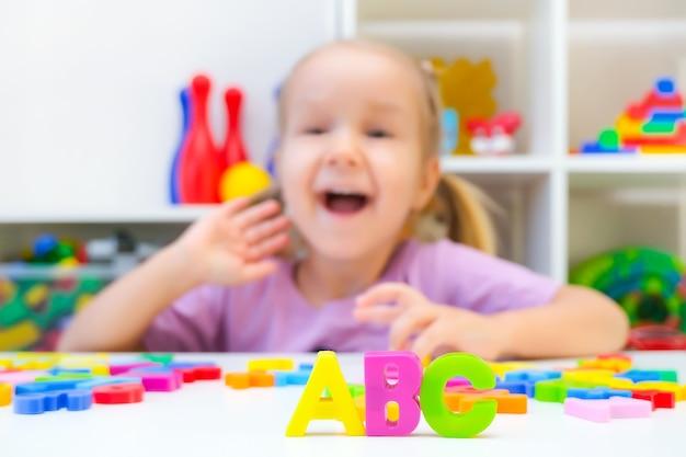 Terapia mowy. maluch dziewczyna z literami. zajęcia z logopedą. abc