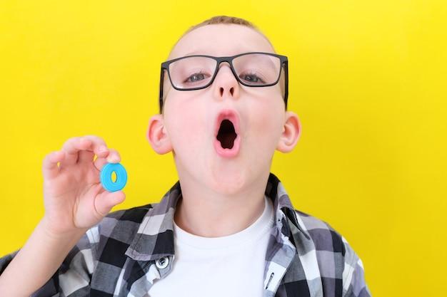 Terapia mowy. maluch mówi literkę o. zajęcia z logopedą. chłopiec na izolowanym żółtym tle