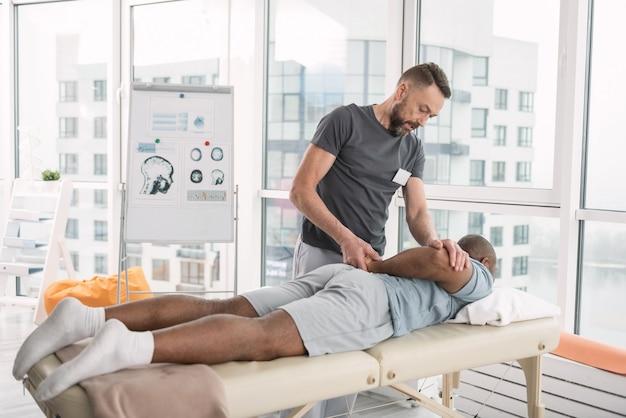 Terapia profesjonalna. mądry profesjonalny terapeuta wykorzystujący specjalną technikę podczas masażu dla swojego pacjenta