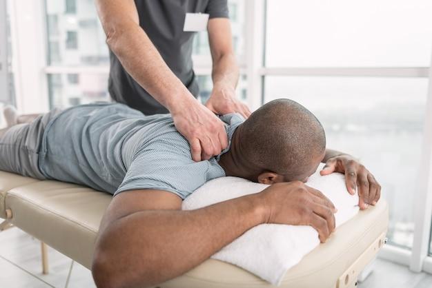 Terapia profesjonalna. miły miły mężczyzna leżący na medycznej kanapie podczas profesjonalnego masażu