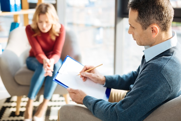 Terapia profesjonalna. smutny przystojny miły mężczyzna trzyma swoje notatki i pisze w tem, słuchając swojego pacjenta