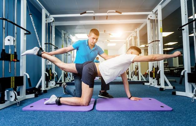 Terapia rehabilitacyjna. młody człowiek robi ćwiczeniom na macie