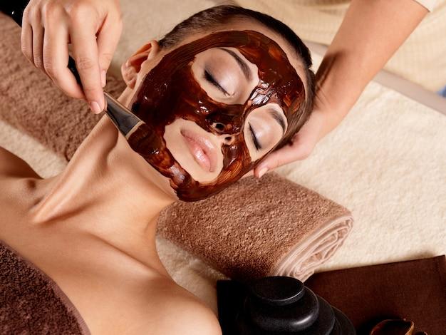 Terapia spa dla młodej kobiety otrzymującej maseczkę na twarz w salonie kosmetycznym - w pomieszczeniach