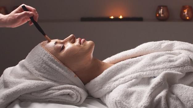 Terapia spa dla młodej kobiety otrzymującej maskę na twarz w salonie kosmetycznym.