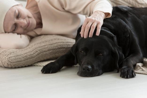 Terapia wspomagana przez zwierzęta zmniejszająca stres u starszej kobiety z rakiem śpiącej z psem na dywanie