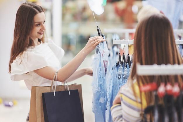 Terapia zakupowa w akcji. tylni widok dwa pięknej kobiety patrzeje each inny z uśmiechem z torba na zakupy podczas gdy chodzący przy sklepem odzieżowym