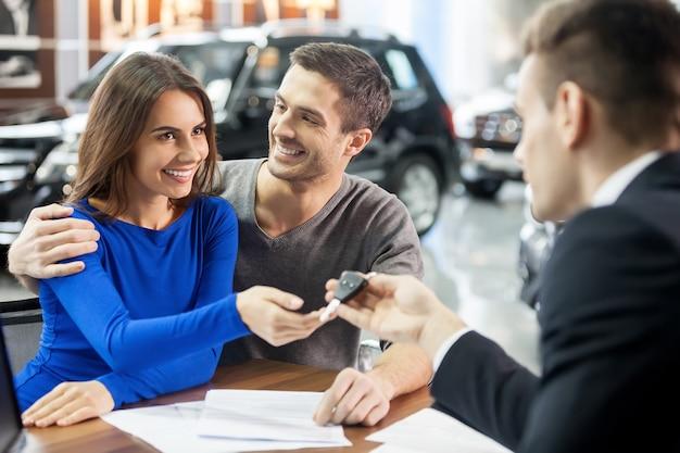 Teraz jej marzenie się spełnia. sprzedawca samochodów wręczający kluczyki do nowego samochodu młodym atrakcyjnym właścicielom