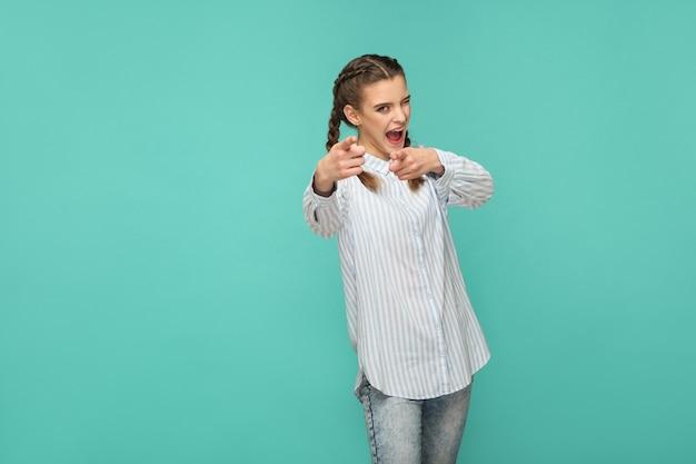 Teraz jest twój czas. portret śmieszne piękna dziewczyna w niebieskie paski t-shirt i warkocz włosów wskazując patrząc na kamery z otwartymi ustami i mrugając. kryty strzał studio na białym tle na zielonym tle.