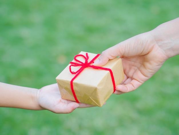 Teraźniejszości, bożych narodzeń i szczęścia pojęcie, - dziecka i matki ręki z prezenta pudełkiem.