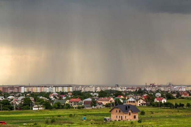 Teren wiejski pod zabudowę zieloną. nowe niedokończone domy z cegły i drewna w odległych wioskach i wysokich budynkach miasta pod pochmurnym niebem. koncepcja budowy i nieruchomości.