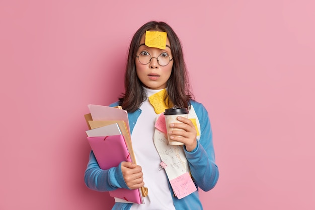 Termin i koncepcja przepracowania. oszołomiona azjatycka pracownica biura pije kawę na wynos.