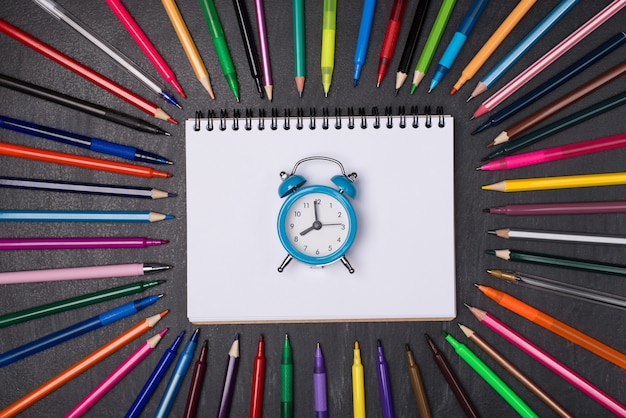 Termin realizacji zadania ostatni pierwszy pierwszy dzwon. zdjęcie z góry nad głową przedstawiające zegar leżący na pustym notatniku otoczony długopisami ołówkami i markerami na tablicy
