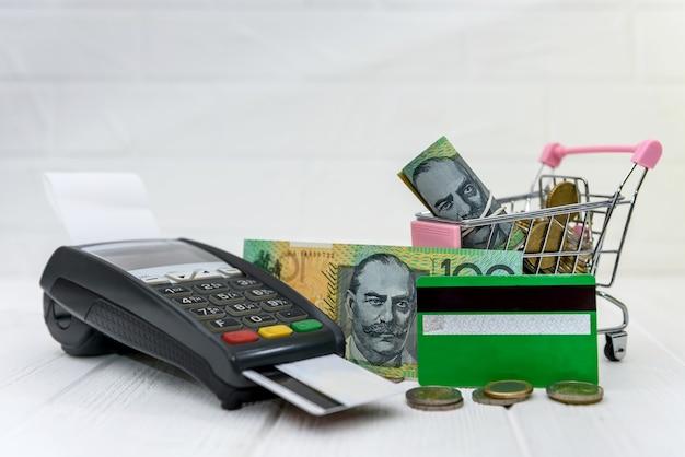 Terminal bankowy z kartą i dolarami australijskimi w koszyku