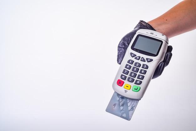 Terminal płatniczy. dłoń w rękawiczce. koncepcja bezpiecznych zakupów