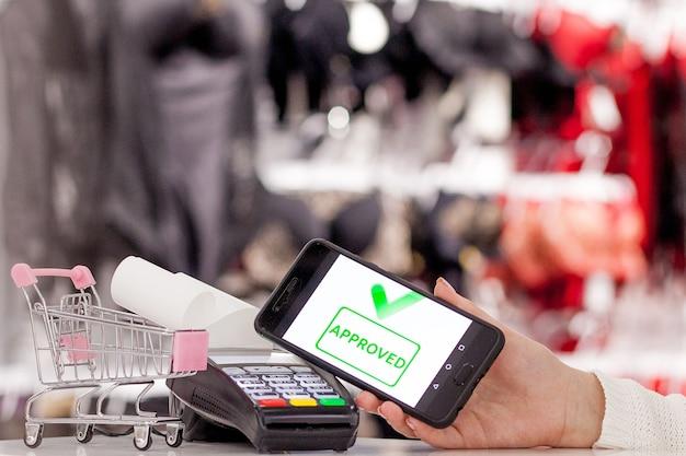 Terminal pos, automat płatniczy z telefonem komórkowym w sklepie. płatności zbliżeniowe w technologii nfc.