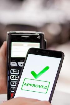 Terminal pos, maszyna płatnicza z telefonem komórkowym na tle sklepu. płatności zbliżeniowe w technologii nfc